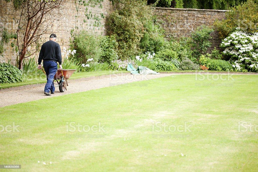 Groundsman pushing wheelbarrow royalty-free stock photo