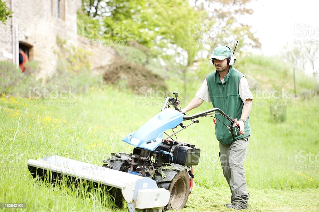Groundsman with mower royalty-free stock photo