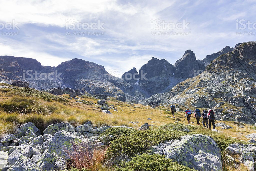 Group backpackers ascending a mountain ridge. stock photo