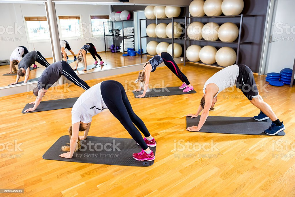 Workout team doing pilates or yoga excerises for flexibility and...
