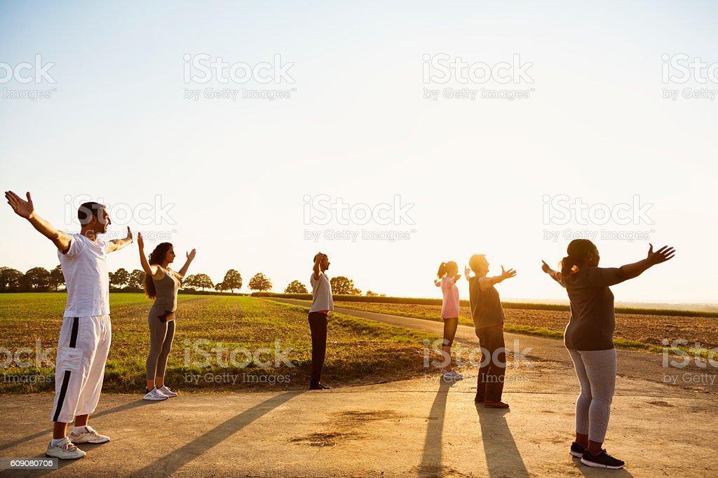 Group exercising Yoga outdoors at sunset stock photo