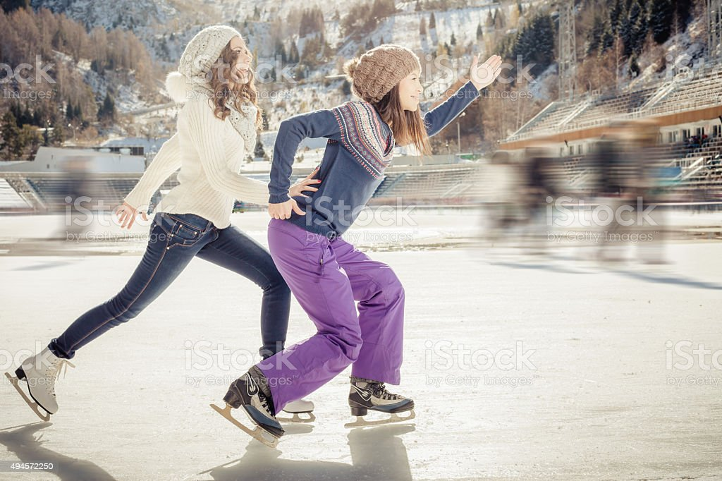 Group funny teenagers ice skating outdoor at ice rink stock photo
