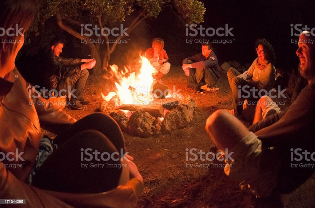 Group gathered around campfire in the woods stock photo