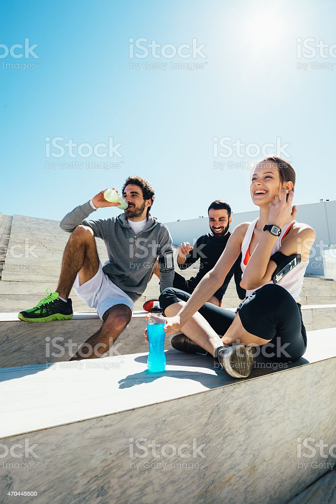 Group having a break from exercise and having drinks stock photo