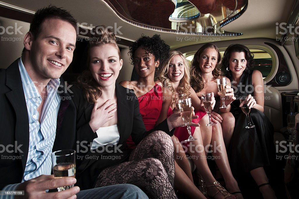 Group  in  a limousine  having drinks on  way   to party royalty-free stock photo
