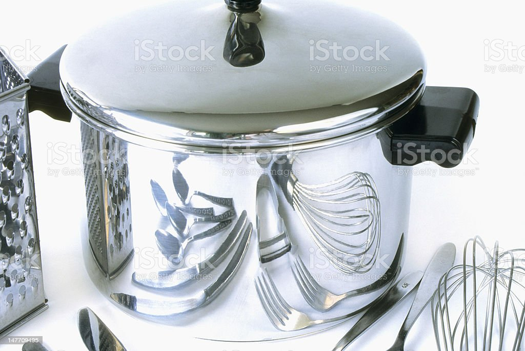 Group kitchen items reflected on side of pot. stock photo