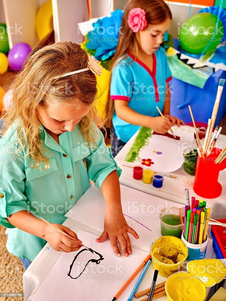 Group little girl with brush painting in  kindergarten stock photo