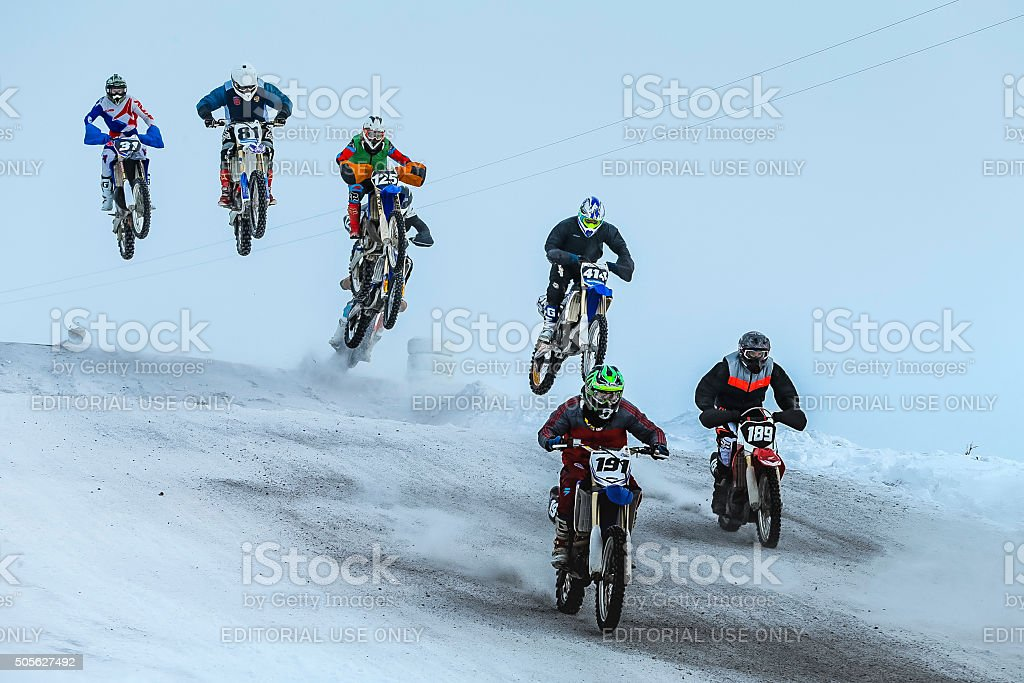 group motorcycle racer riding on snow-covered mountain after start stock photo