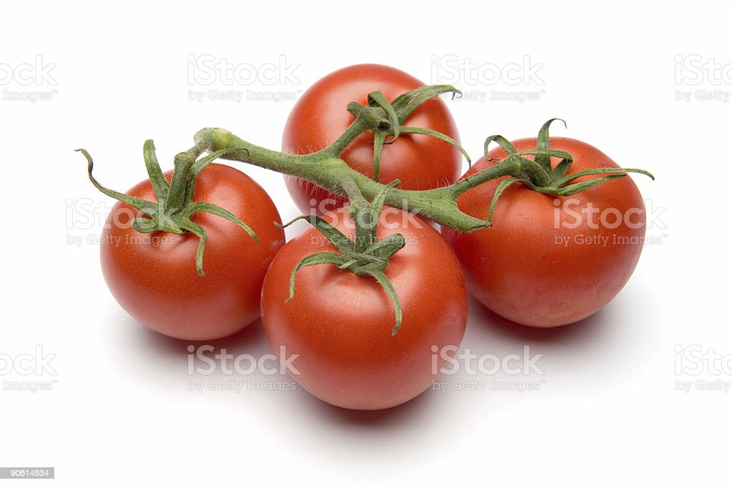 A group of 4 red tomatoes still attached to the vine stock photo