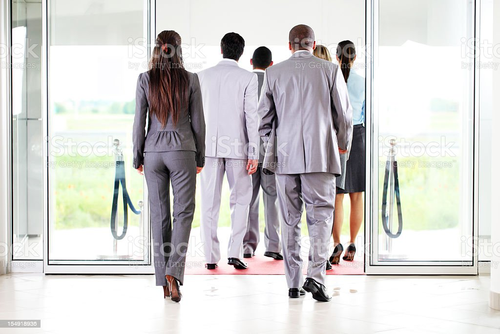 Group of a business people going away from workplace. stock photo