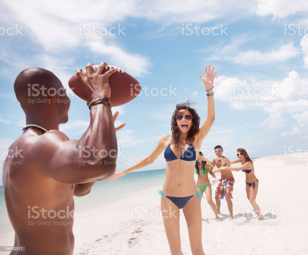 Group of a friends playing rugby on beach against sky royalty-free stock photo