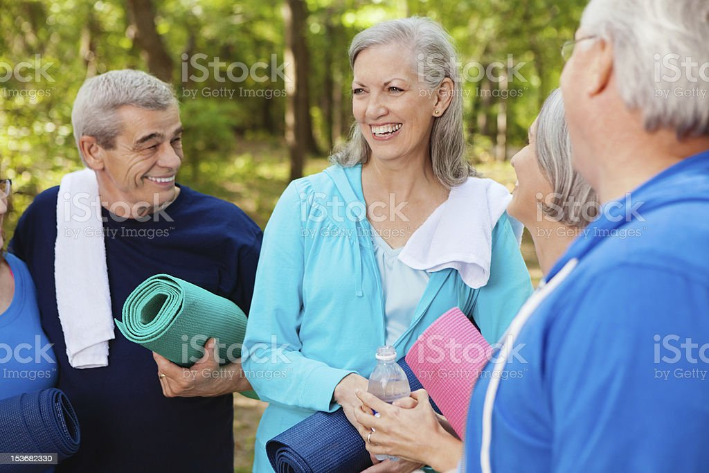 Group of active seniors laughing together during outdoor fitness class royalty-free stock photo