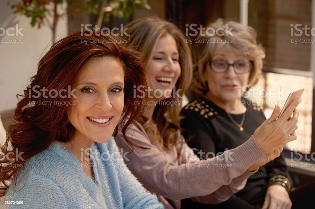 Group of adult and senior women with phone stock photo