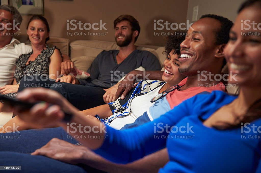 Group of adult friends watching television together stock photo