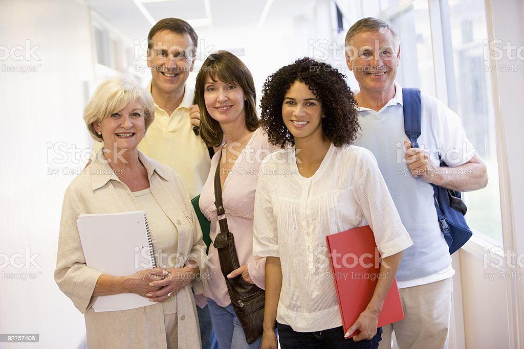 Group of adult students standing in campus corridor stock photo