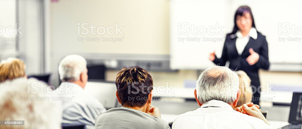 Group of adult students with female teacher explaining stock photo