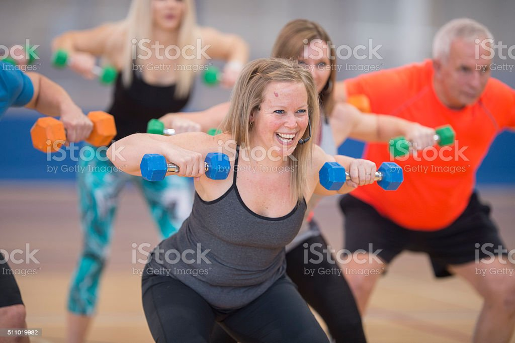 A group of adults are taking a fitness class together stock photo