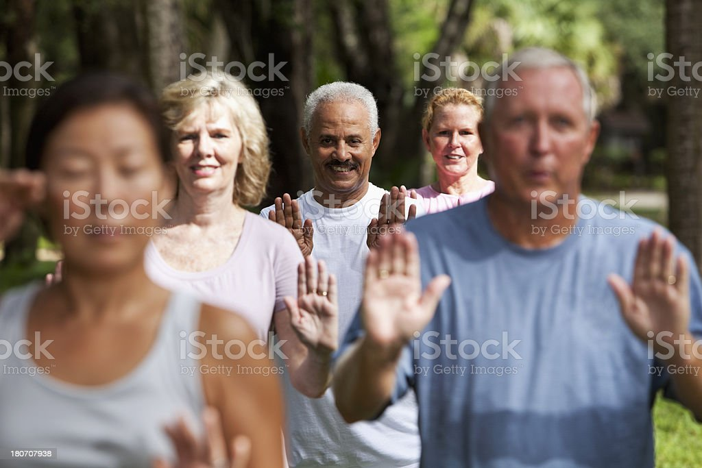 Group of adults exercising in park stock photo