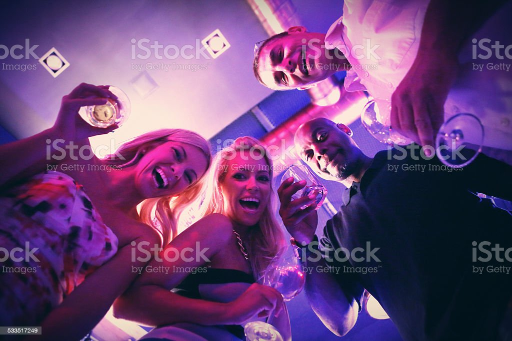 Group of adults having fun in club on weekend night. stock photo