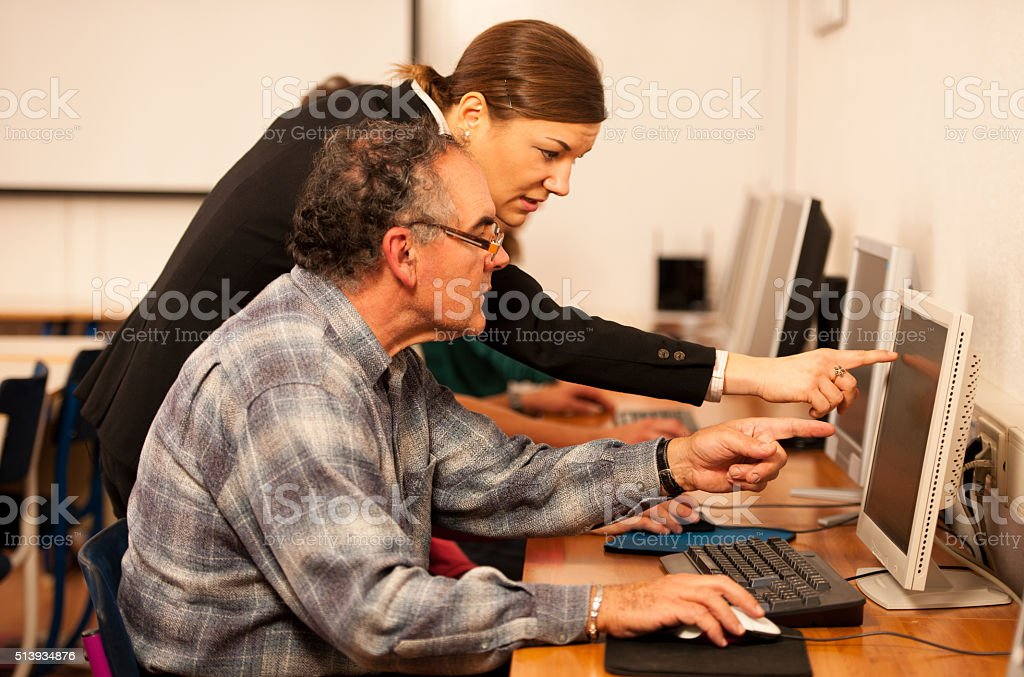 Group of adults learning computer skills. Intergenerational transfer of knowledge. stock photo