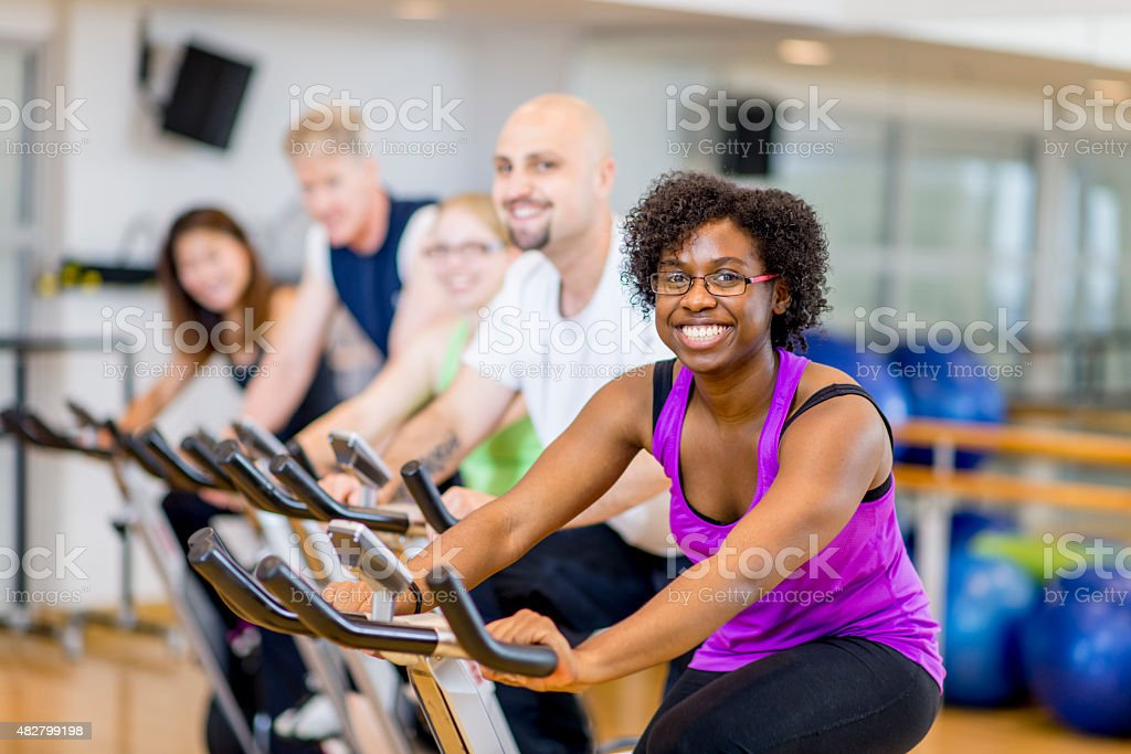 Group of Adults on Exercise Bikes in Fitness Class stock photo