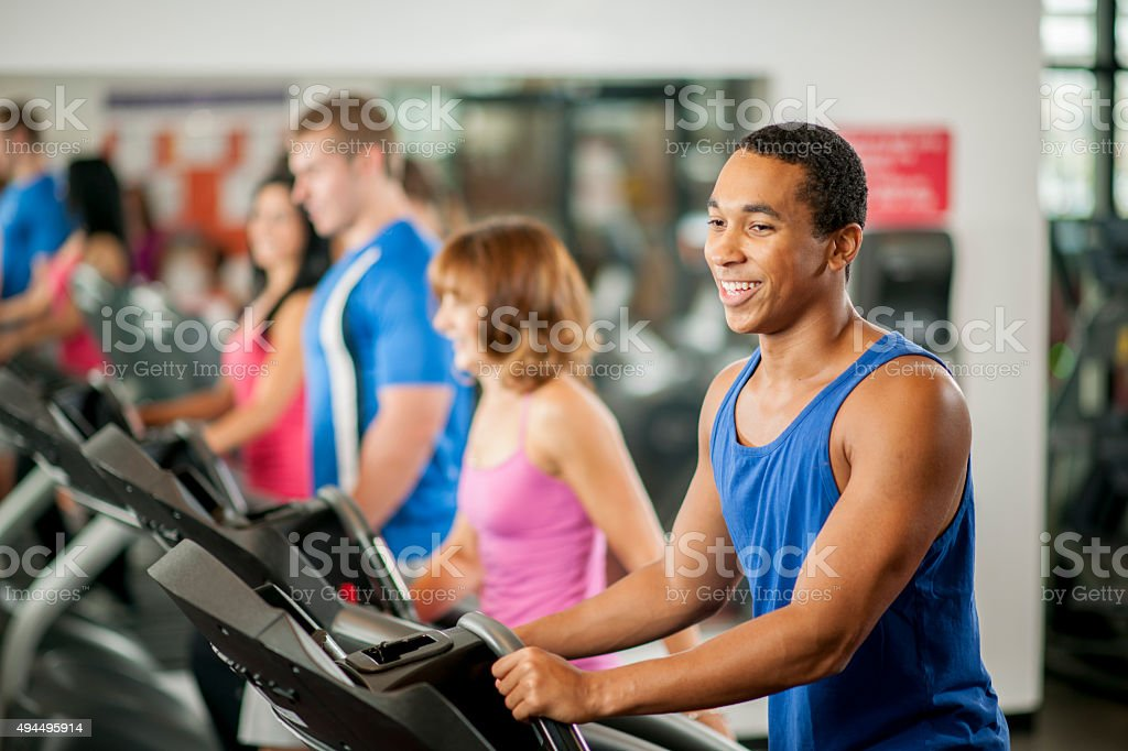 Group of Adults on Workout Machines in the Gym stock photo