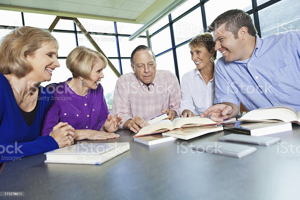 Group of adults reading in a library together royalty-free stock photo