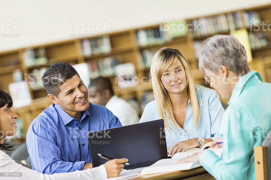 Group of adults studying in library to continue education royalty-free stock photo