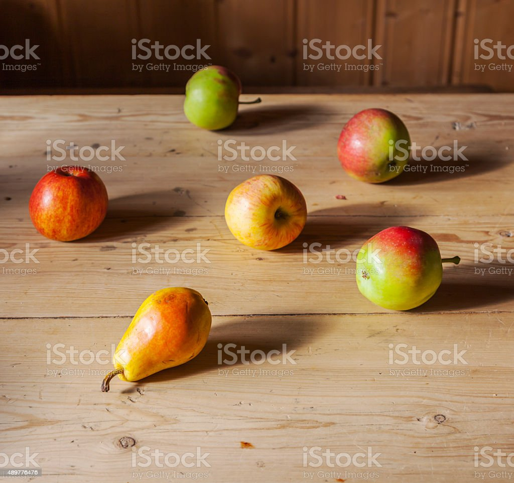 Group of apples and pears spread on antique wooden table. stock photo