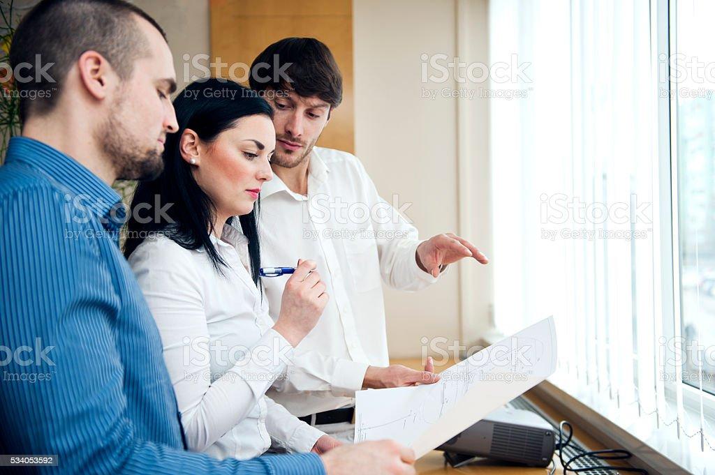 Group of  architects  analyzing blueprint plans stock photo