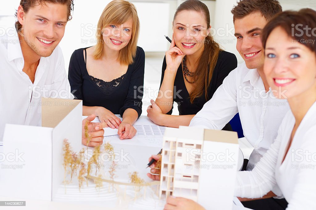 Group of architects gathered with architectural models and sketches royalty-free stock photo