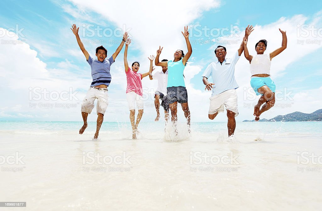 Group of Asians jumping on the tropical beach. royalty-free stock photo