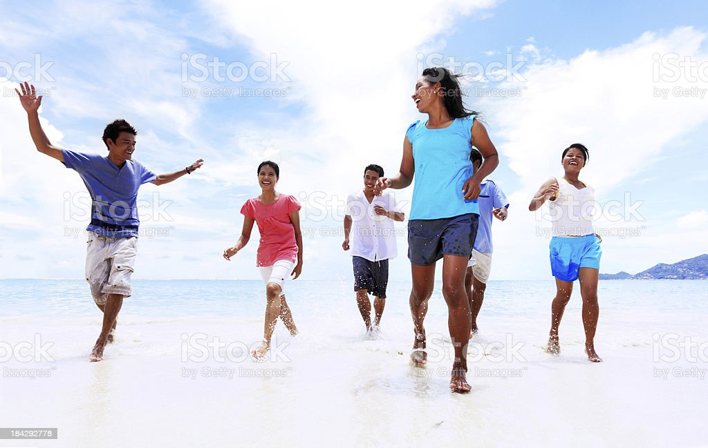 Group of Asians people running on the beach. royalty-free stock photo