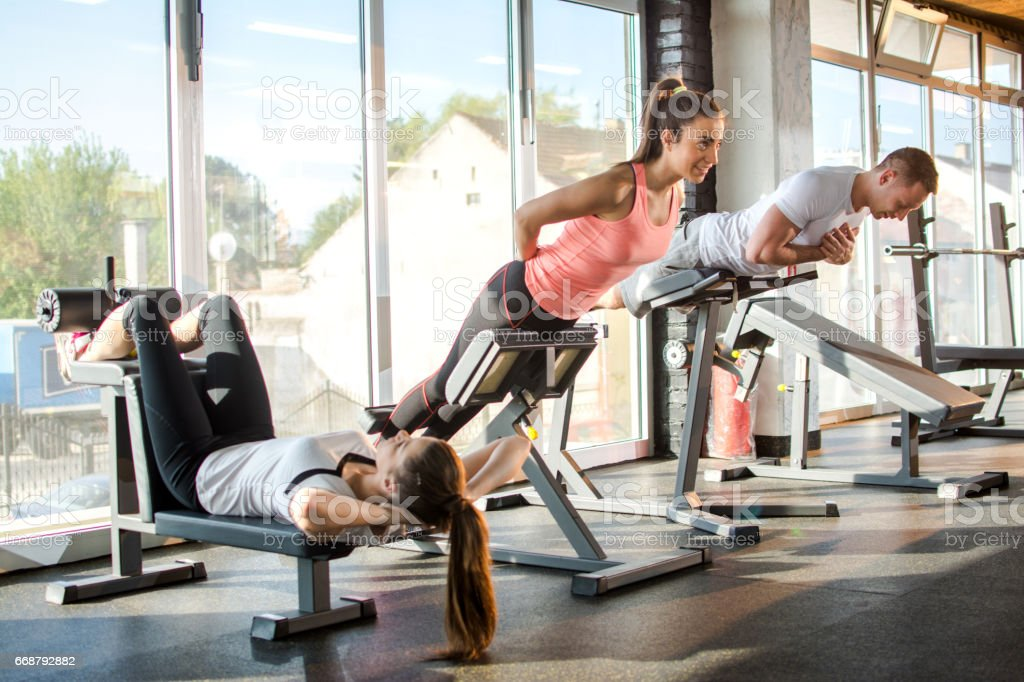 Group of athletes doing strength exercises on gym machines in fitness center. stock photo