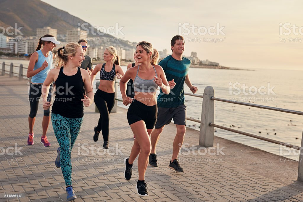 Group of athletes running along a seaside promenade stock photo