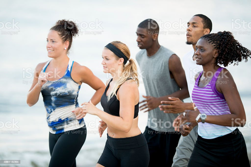 Group of Athletes Running Together Outside stock photo