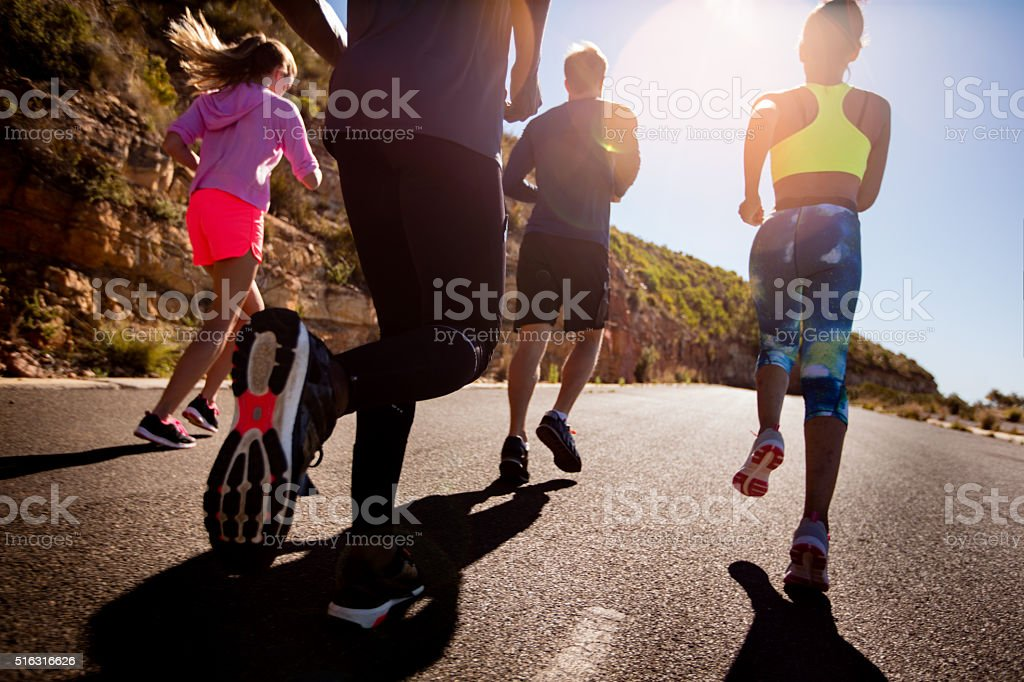 Group of athletic friends running outdoors stock photo