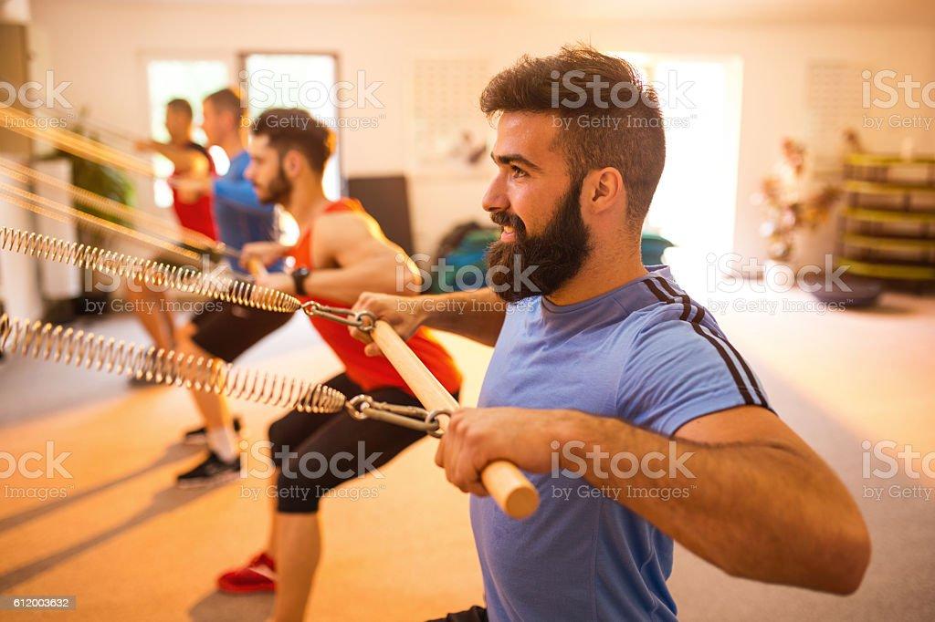 Group of athletic men exercising on Pilates machines. stock photo