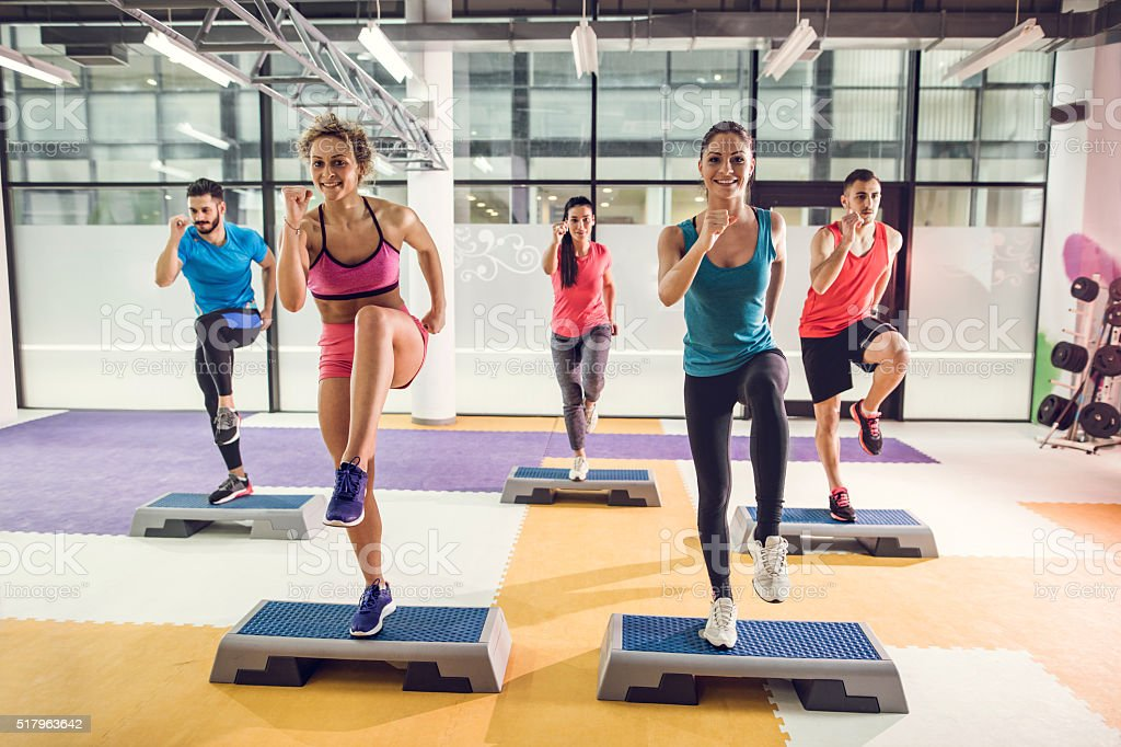 Group of athletic people exercising step aerobics in a gym. stock photo