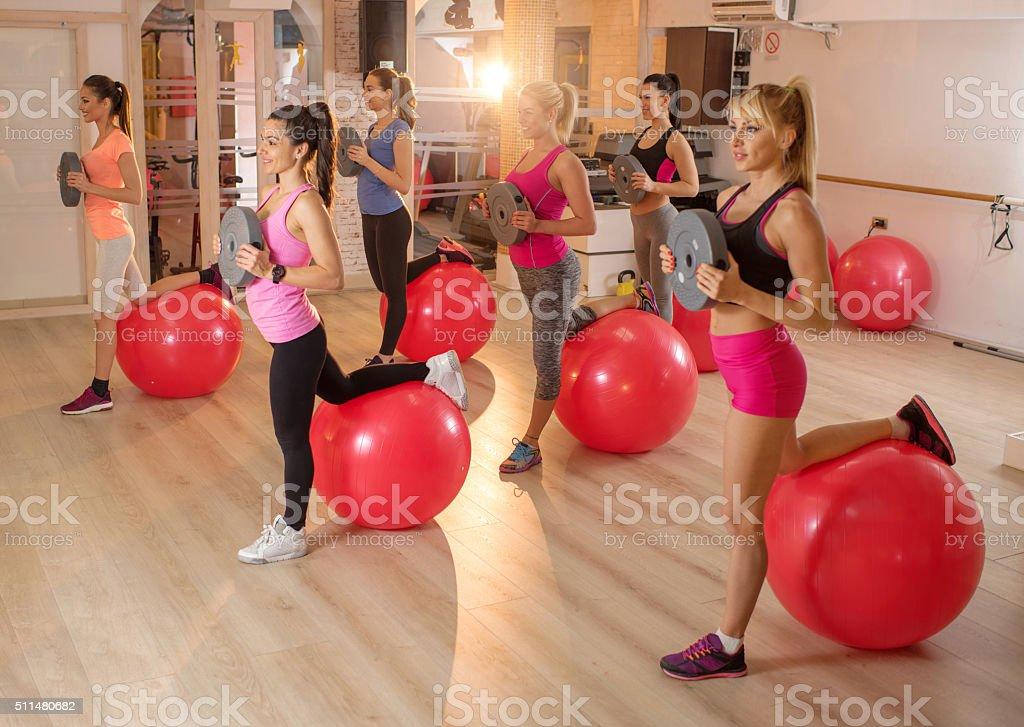Group of athletic women exercising on aerobics class. stock photo