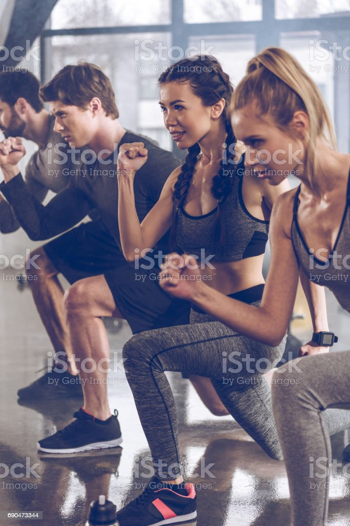 group of athletic young people in sportswear doing lunge exercise at the gym, aerobic fitness concept stock photo