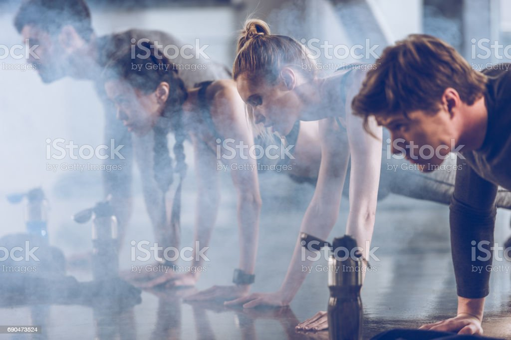 group of athletic young people in sportswear doing push ups or plank at the gym, group fitness concept stock photo