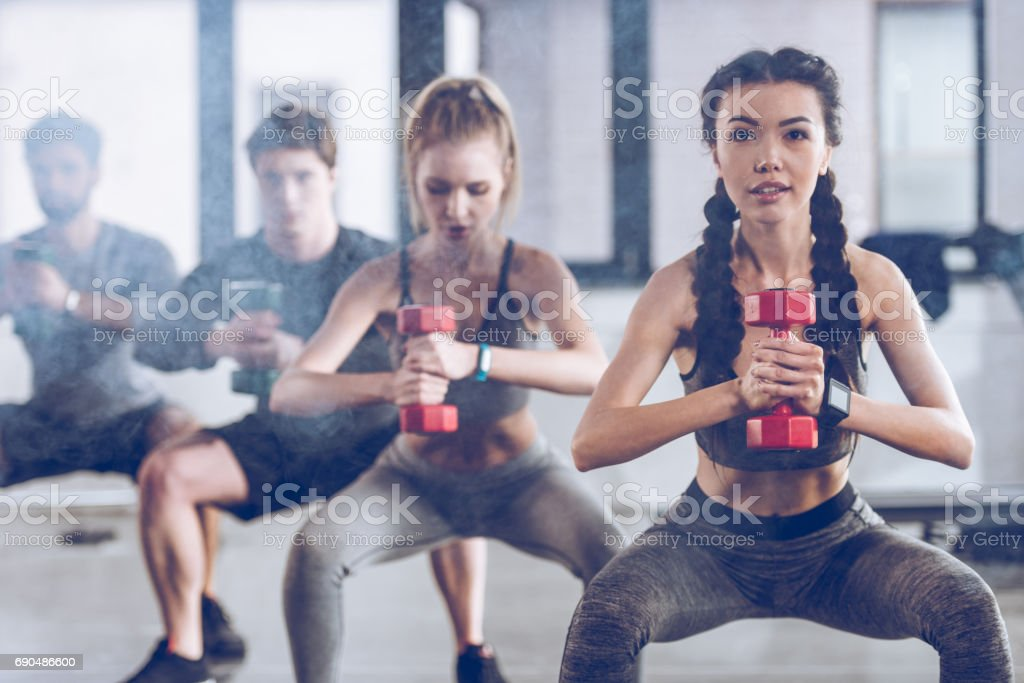 group of athletic young people in sportswear with dumbbells squatting and exercising at the gym stock photo