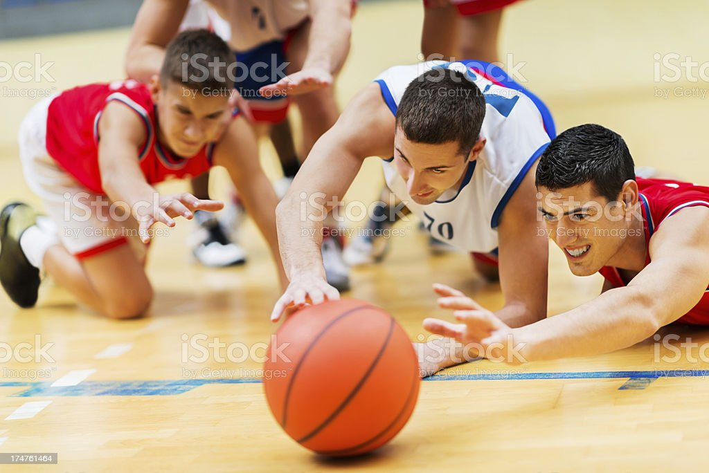 Group of basketball players reaching for the ball. royalty-free stock photo