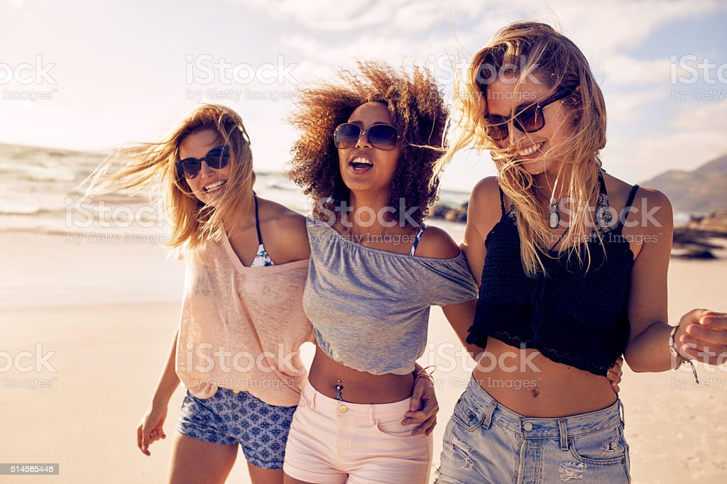 Group of beautiful young women strolling on a beach stock photo