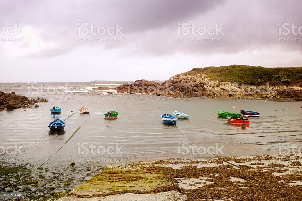 Group of boats mooring in a small fishing harbor . stock photo