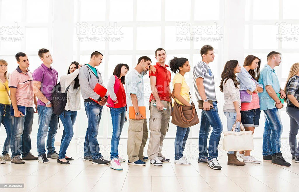Group of bored students standing in a line and waiting. stock photo