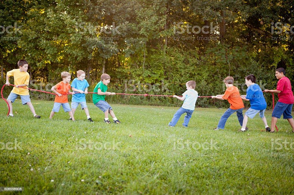 Group of Boys Playing Tug of War Outside stock photo