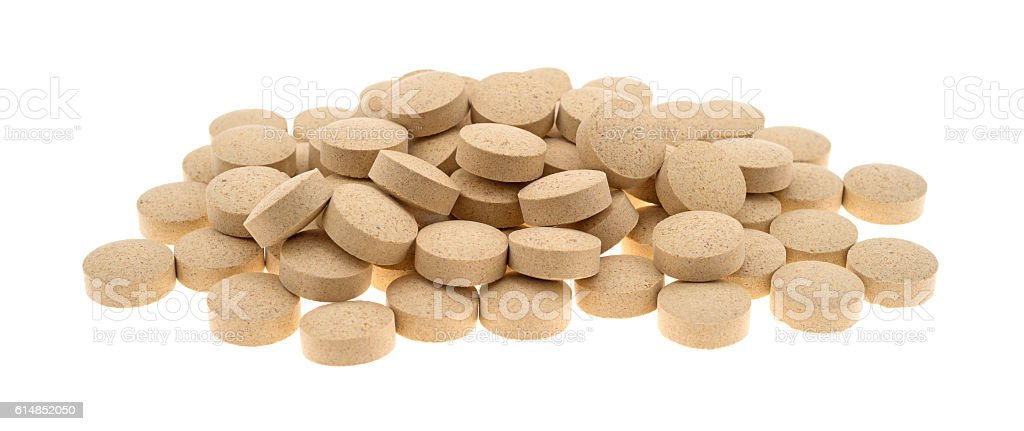 Group of brewer'€™s yeast nutritional supplement tablets on whit stock photo