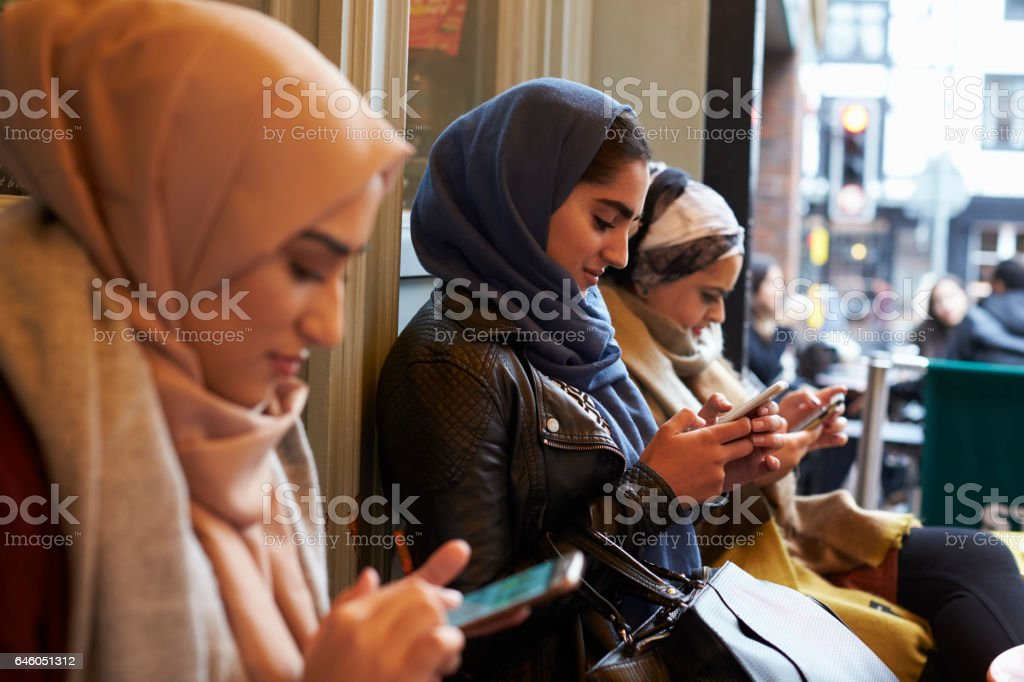 Group Of British Muslim Women Texting Outside Coffee Shop stock photo